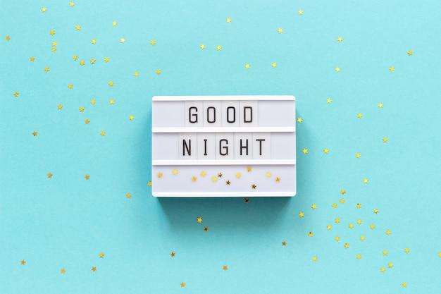 ライトボックスのテキストおやすみと青い紙の背景に金の星。