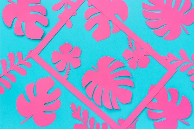 熱帯の葉のパターン。紙と青い背景上のフレームのトレンディなピンクの熱帯の葉