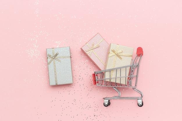 Корзина, тележка и подарочные коробки пастельных цветов на розовом фоне