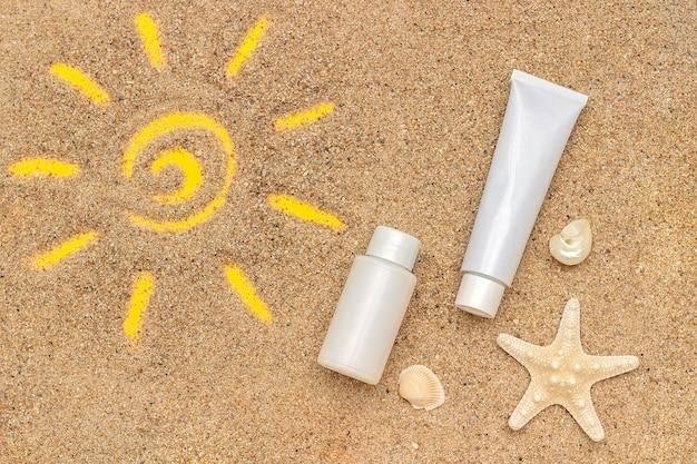Знак солнца нарисованный на песке, морской звезде и белой пробке, бутылке солнцезащитного крема.