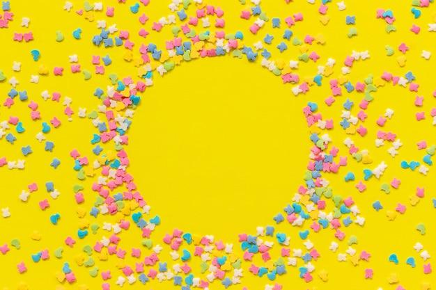 黄色い紙の上の散乱多色菓子トッピングドレッシング。サークルフレームのお祭りの背景