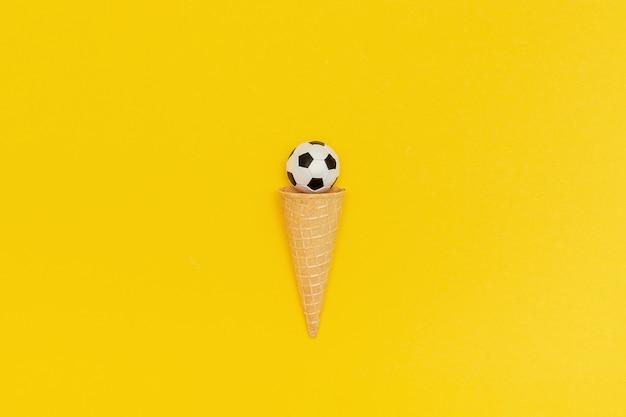 黄色の背景にアイスクリームコーンのサッカーまたはフットボールのボール。