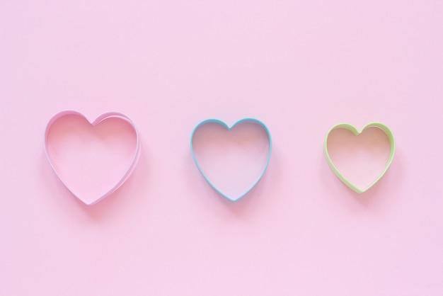 パステルピンクの背景にハート形のカラフルなカッタークッキー。コンセプトバレンタインカード。