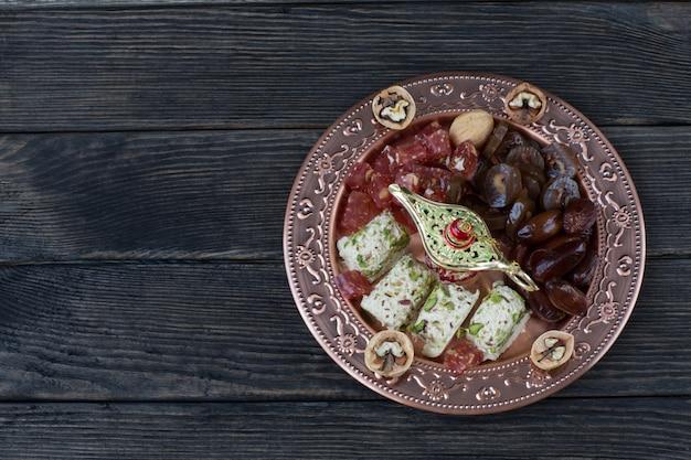 В бронзовой тарелке финики, грецкие орехи, халва, лукум и грецкие орехи