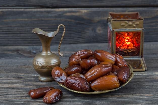 В бронзовой тарелке финики, кувшин и фонарь. рамадан карим.