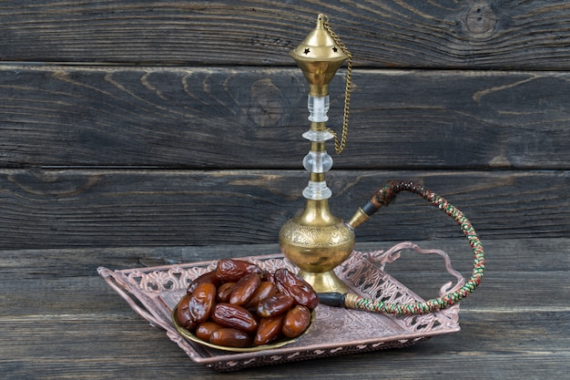 В бронзовой тарелке финики и кальян. рамадан карим.