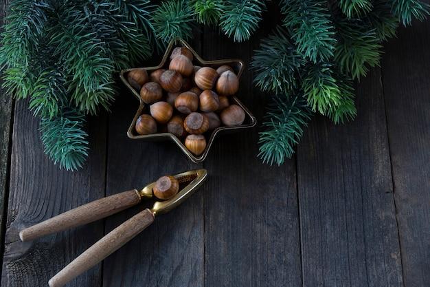Орехи в бронзовой вазе в форме звезды, старый щелкунчик и сосновые ветки вокруг
