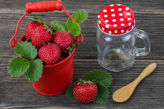 バケツの中でイチゴ、スプーン、ガラスの瓶のクローズアップ(調理ジャム)