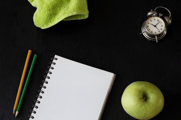 学校の黒の背景上の項目:ぼろ、ノート、鉛筆、りんご、目覚まし時計