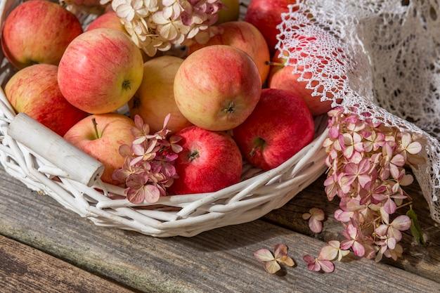 白い古いバスケット(クローズアップ)で太陽の下で木製のテーブルにピンクのリンゴ