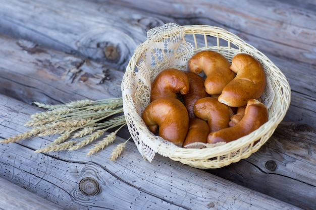 枝編み細工品バスケットに新鮮なパイとライ麦の耳の近くに