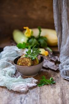 Блины из кабачков в керамической тарелке на деревянном столе