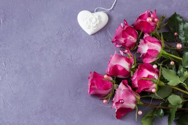 ピンクのバラの花束と白い漆喰の心