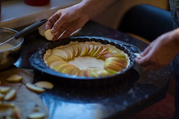 Женщина руками кладет яблоки на тесто на кухне