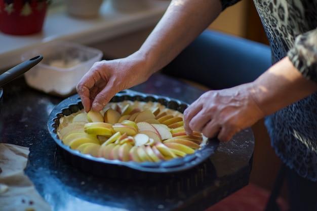 女性の手が生地にリンゴを置く