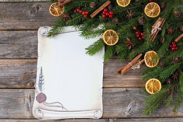 Ветви ели, корицы, аниса, дольки лимона, красные ягоды и лист бумаги