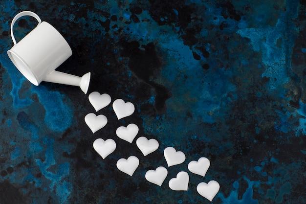 На синем фоне белая лейка и белые сердца летят из нее