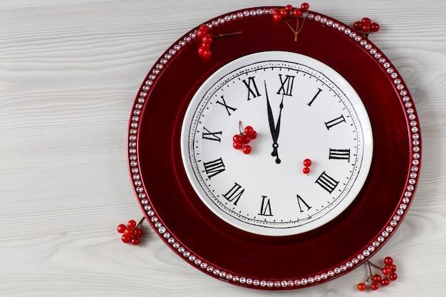 Красная тарелка и белая тарелка с изображением часов и красных ягод