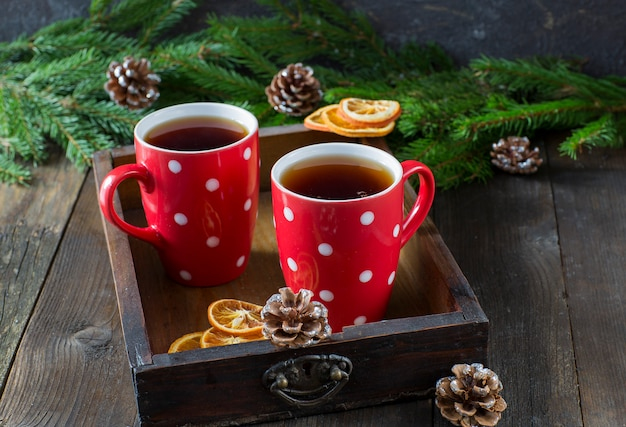 Чай в красных кружках и еловых ветках, шишках