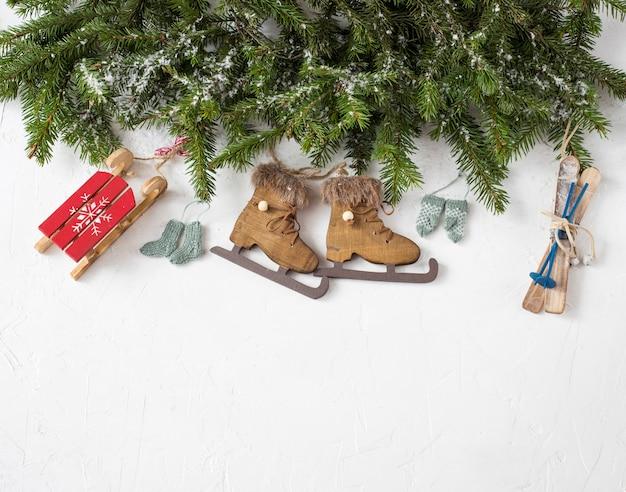 松の枝とクリスマスの装飾:ミトン、靴下、スケート、スキー、そり