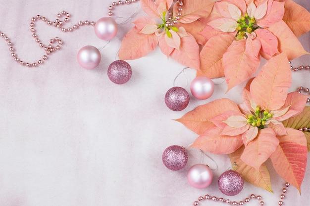 ピンクの背景にピンクのポインセチア、ボール、ビーズ