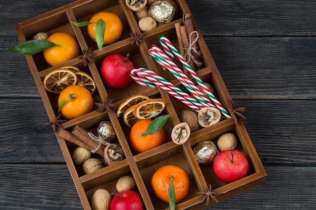 В деревянной коробке: мандарины, яблоки, грецкие орехи, корица и леденцы