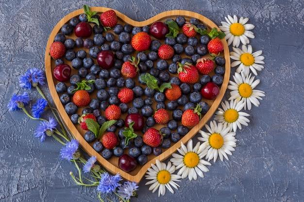 На сером фоне деревянное сердечко и в нем летние ягоды