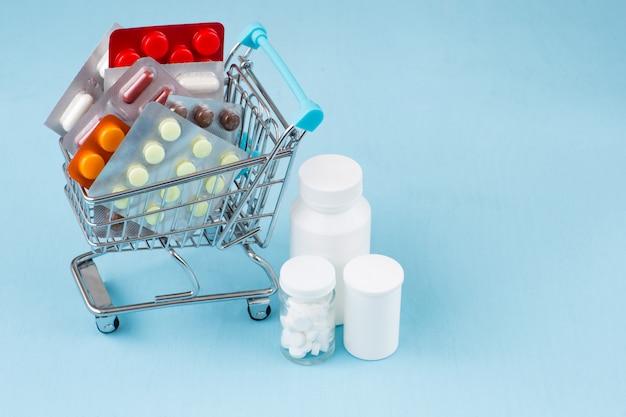 Игрушечная тележка, полная упаковок таблеток, рядом со шприцами, маской и лекарствами