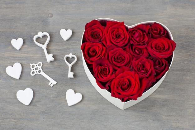 В коробке в форме сердца бутоны красных роз и декор: сердечки, ключи