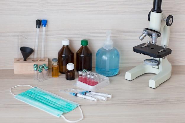 テーブルの上:アンプル、注射器、防護マスクのワクチン
