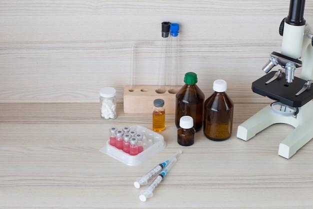 テーブルの上:アンプル、シリンジ、顕微鏡、錠剤のワクチン