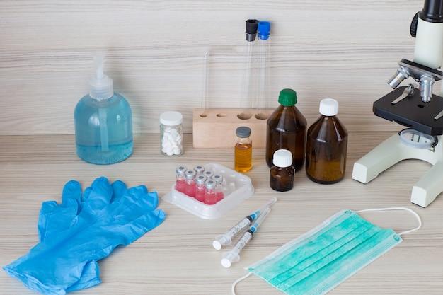 テーブルの上:手の消毒器、手袋、アンプルワクチン、注射器、フェイスマスク、顕微鏡、錠剤