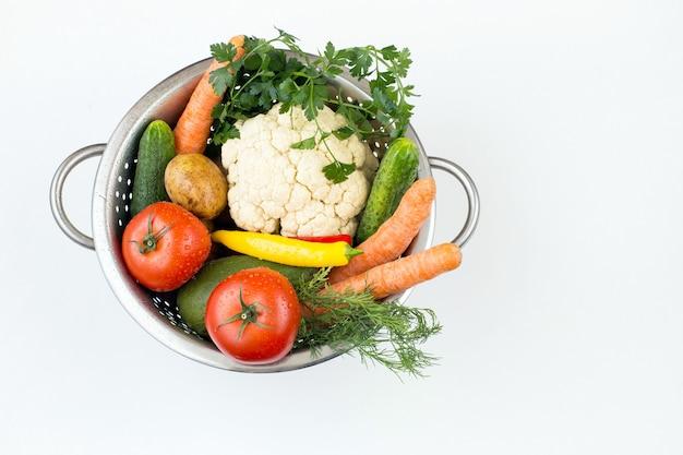 Свежие овощи в дуршлаге на белом столе
