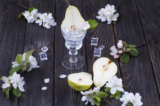 Срезанные груши, бокалы, лед и цветы груши
