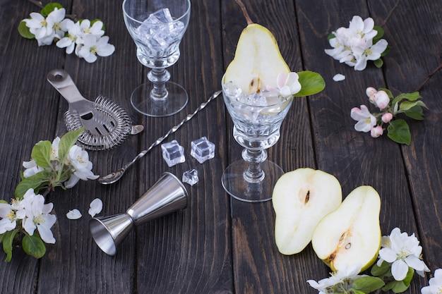 Нарезанные груши, бокалы, лед, предметы для приготовления коктейля в баре и цветы груши