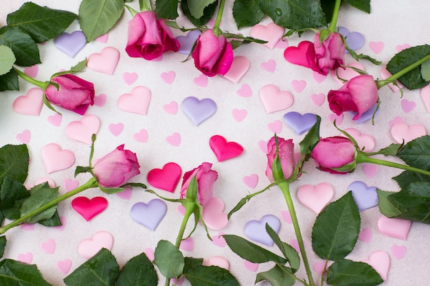 На розовом фоне по кругу разложены разноцветные сердечки из атласа и розовых роз
