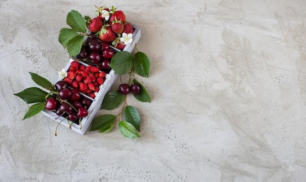 桜、森のイチゴ、灰色の背景上の木製の箱のイチゴ