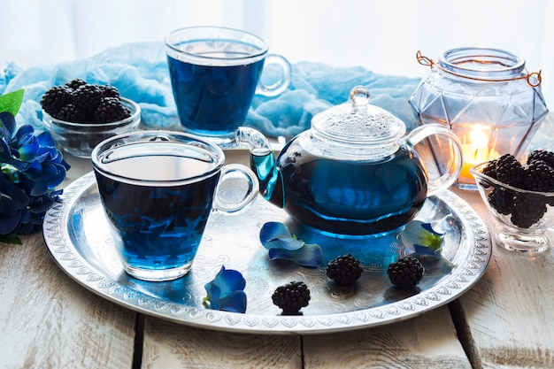 透明なカップ、ブラックベリーの白い木製のテーブルブルーティーに