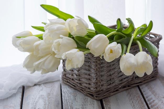 На столе корзина с белыми тюльпанами