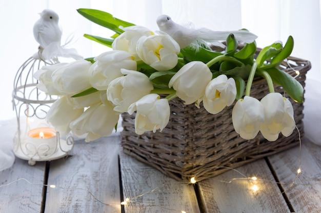 テーブルの上の白いチューリップ、白い鳥、ローソク足、ライト付きバスケット