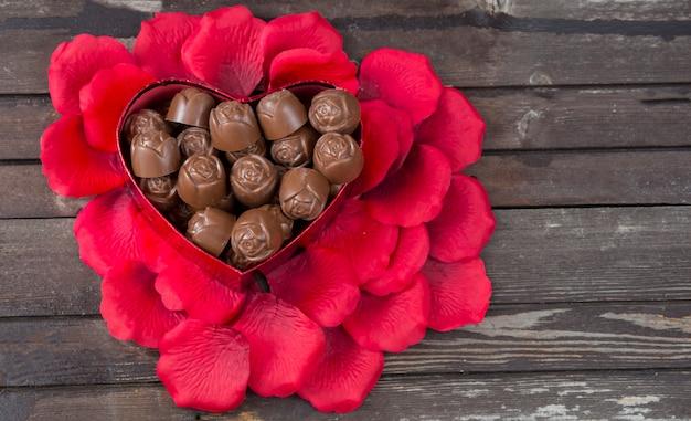 バラの花びら、暗い背景の木にハートの形のキャンディー
