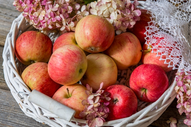 テーブルの上の白いバスケットに太陽の下でピンクのりんご
