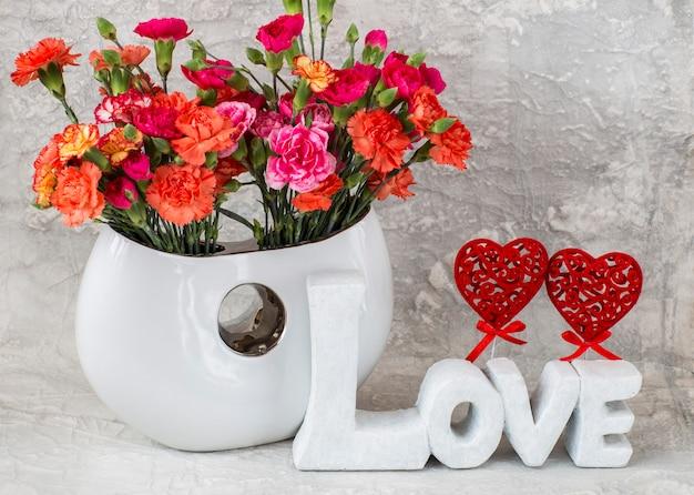 灰色の背景上の白い花瓶に明るいカーネーション