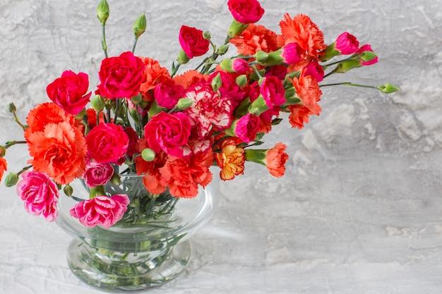 灰色の背景上の花瓶に明るいカーネーション