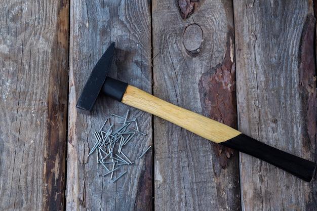 Молоток и гвозди на деревянном столе