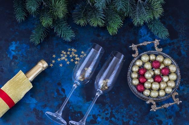 花瓶、金と赤のボール、ゴールデンリボン、シャンパンのボトルで暗い青色の背景に
