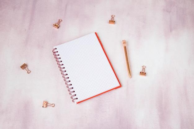 ピンクの背景のメモ帳、ペーパークリップ、ローズゴールドのペン