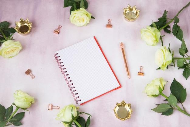 ピンクの背景のメモ帳、バラ、クラウン、クリップ、ペン