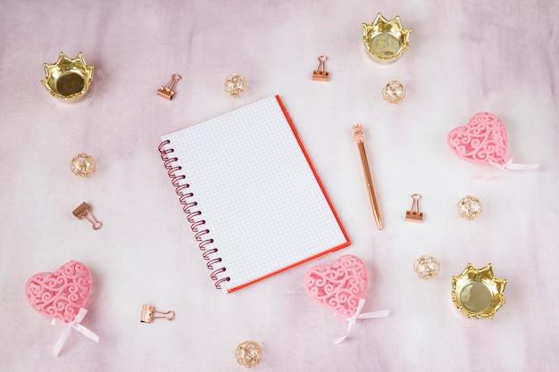 На розовом фоне блокнот, коронки, скрепки, ручка - планирование девичника, свадьбы, дня рождения