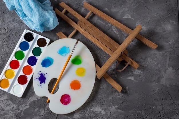 На столе, предметы для рисования: палитра, кисть, краски